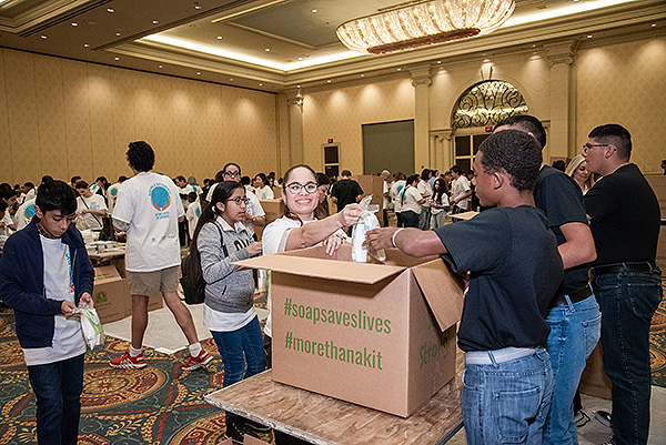 Volunteers packaging the Clean the World kits